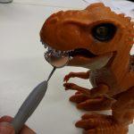 Dinosauruslelun suuta tutkitaan hammaslääkärin peilillä.