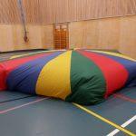 Lapset tekivät leikkivarjosta teltan ja istuvat sen alla.