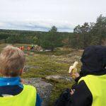 Lapset syövät eväitä korkealla kalliolla ja edessä näkyy kaunis maisema.