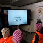 Lapset katsovat isolta screeniltä kuvaa.