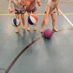 Kolme lasta pomputtaa koripalloja.