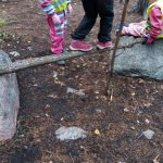 Lapsi tasapainottelee kahden kiven päällä olevan puunrungon päällä.