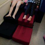 Kaksi lasta istuu päällekäin kasattujen lattiatyynyjen päällä.