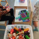 Lapset leikkivät kassakoneella ja leikkiruuilla.