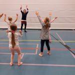 Lapset tanssimassa liikuntasalissa.