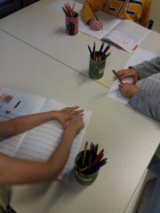 Lapset harjoittelevat L-kirjaimen kirjoittamista.