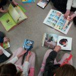 Lapsia lattialla kirjojen kanssa.
