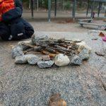 Kivistä ja kepeistä tehty leikkinuotio.