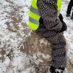 Lapsi istuu lumipallon päällä.