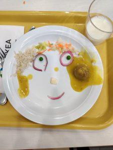 Lautanen jossa ruoka on asteltu kasvojen muotoon.