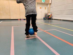 Lapsi hyppää pallo nilkkojen välissä.