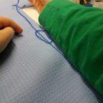 Lapsi ompelee vohvelikangasta.