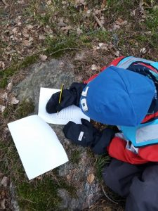lapsikirjoittaakivenpäälläpaperille.