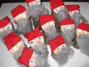 Kuvassa lasten askartelemia puusta tehtyjä tonttuja, punainen tonttulakki ja harmaa parta.