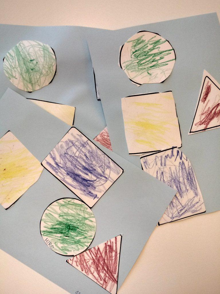 Kuvassa lasten värittämiä ja leikkaamia muotoja. keltainen neliö,sinen suorakulmio,vihreä ympyrä