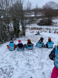 Lapset istuvat rivissä liukurimäen yläpuolella odottamassa omaa vuoroa.