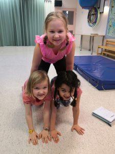 Kolme lasta on muodostanut kehoistaan pyramidin.