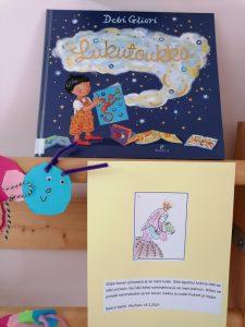 Lukutoukka kirja ja lapsen keksimä prinsessasatu.