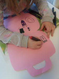 Lapsi piirtää kartongista leikattuun matkalaukkuun vaatteita.