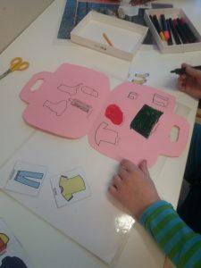 Lapsi piirtää vaatteita kartongista askarreltuun matkalaukkuun.
