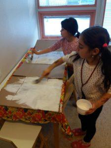 Lapset maalaavat isoa pahvia valkoiseksi.