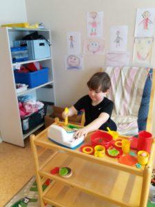 Lapsi leikkii kahvilaa leikkiastioilla.