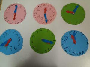 Seinällä kartongista askarrellut kellot.