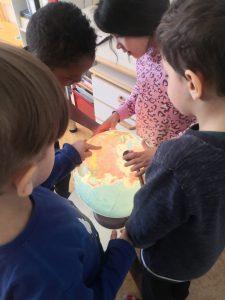 Lapset tutkivat karttapalloa.