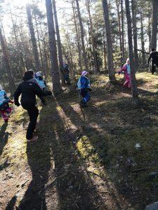 Lapset juoksevat metsässä leikkimässä kuka pelkää metsästäjä -leikkiä.