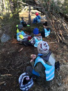 Lapset istuvat metsässä syömässä eväitä.