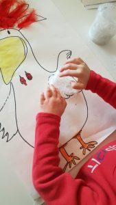 Lapsi liimaa höyheniä kana-askarteluun.