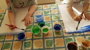 Kuvassa lapset maalaavat vesiväreillä.