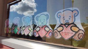 Kuvassa lasten värittämät nallekuvat ikkunassa.