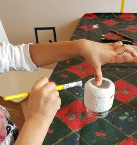 Kuvassa lapsi maalaa lasipurkkia valkoiseksi.