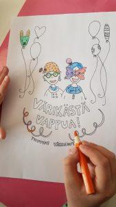 Kuvassa lapsi värittää värityskuvaa, jossa lukee värikästä vappua.