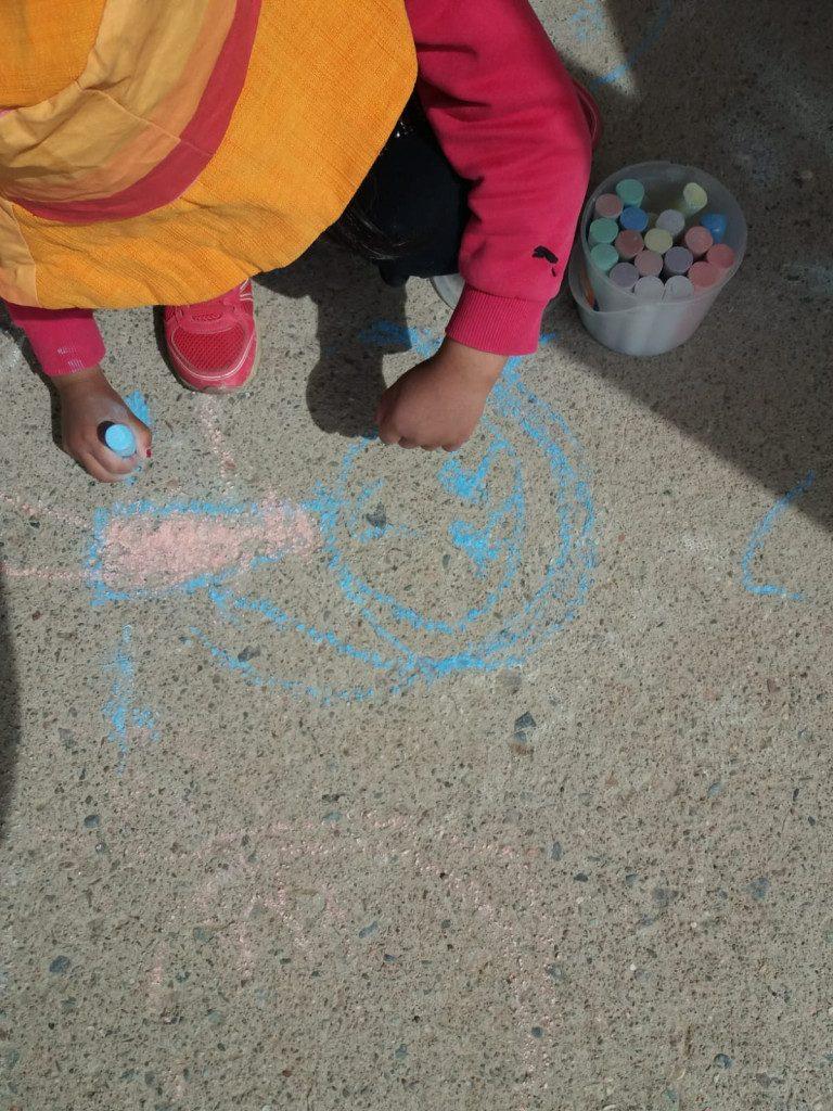 Kuvassa lapsi piirtää katuliiduilla.