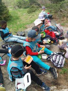 Lapset istuvat maassa syöden omia eväitä.