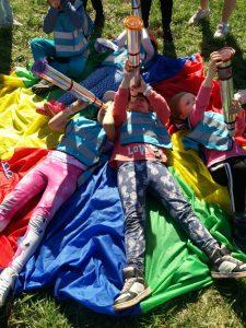 Lapset makaavat viltillä ja tutkivat taivasta itsetehdyillä kaukoputkilla.