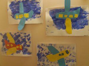 Vesivärein maalattu taivas jossa paperista liimattu lentokone.