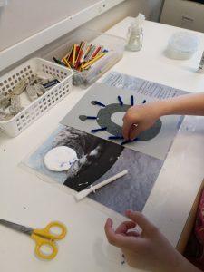 Lapsi askartelee ö-kirjaimen mallista ötökkä askartelua.