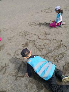 Lapset piirtävät kepillä hiekkaan omia kuviaan.