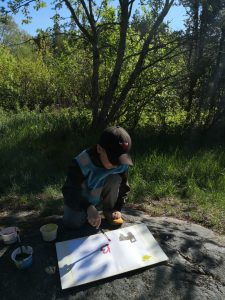 Lapsi maalaa kalliolla.