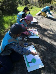 Lapset maalaavat metsässä.