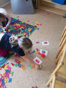 Lapset lajittelevat muovikirjaimia: H, D ja G.
