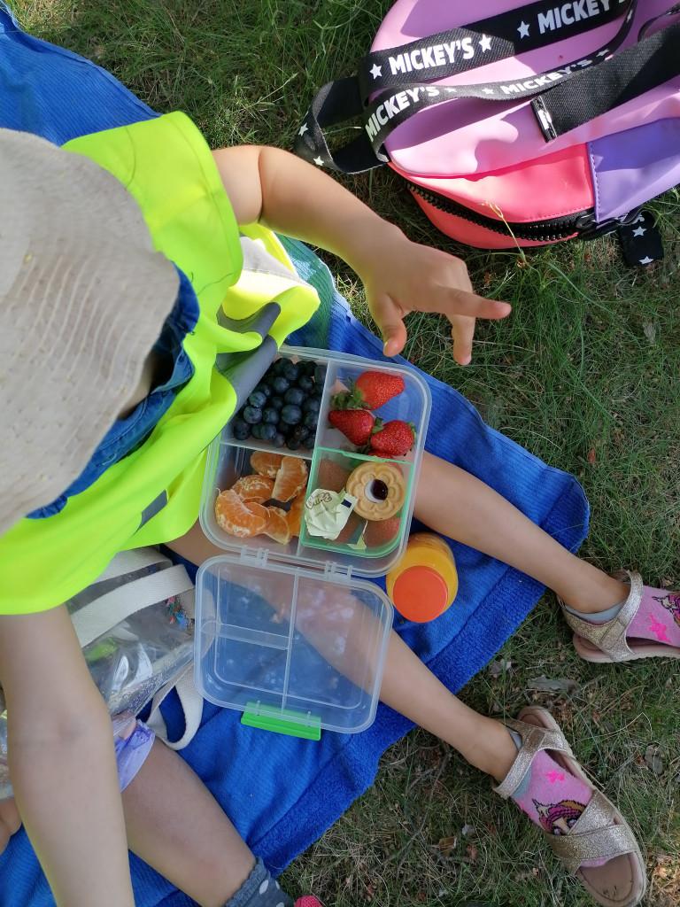 Lapsi istuu metsässä ja syö eväitä.