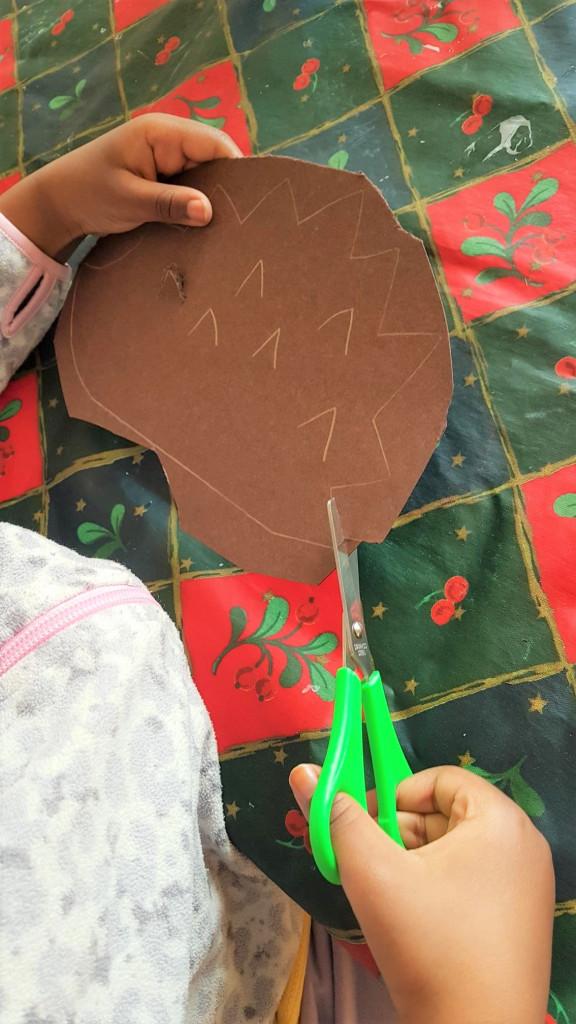 Lapsi leikkaa kartongista siilin muotoa irti.