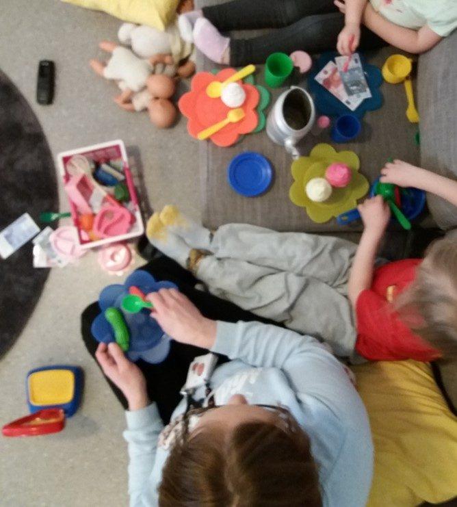 lapset istuvat sohvalla ja syövät leikkiruokaa.