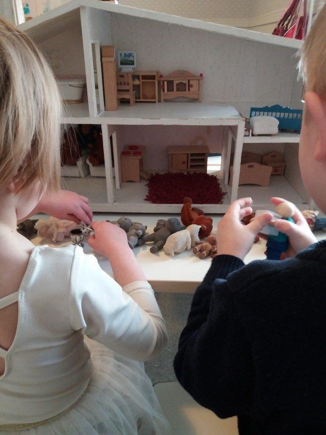 kaksi lasta leikkii nukkekodilla.