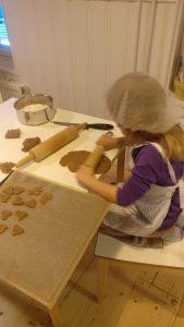 lapsi leipoo pipareita pöydän ääressä.