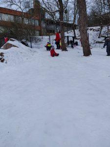 kaksi lasta ja hoitaja laskevat liukurilla lumisesta mäestä.